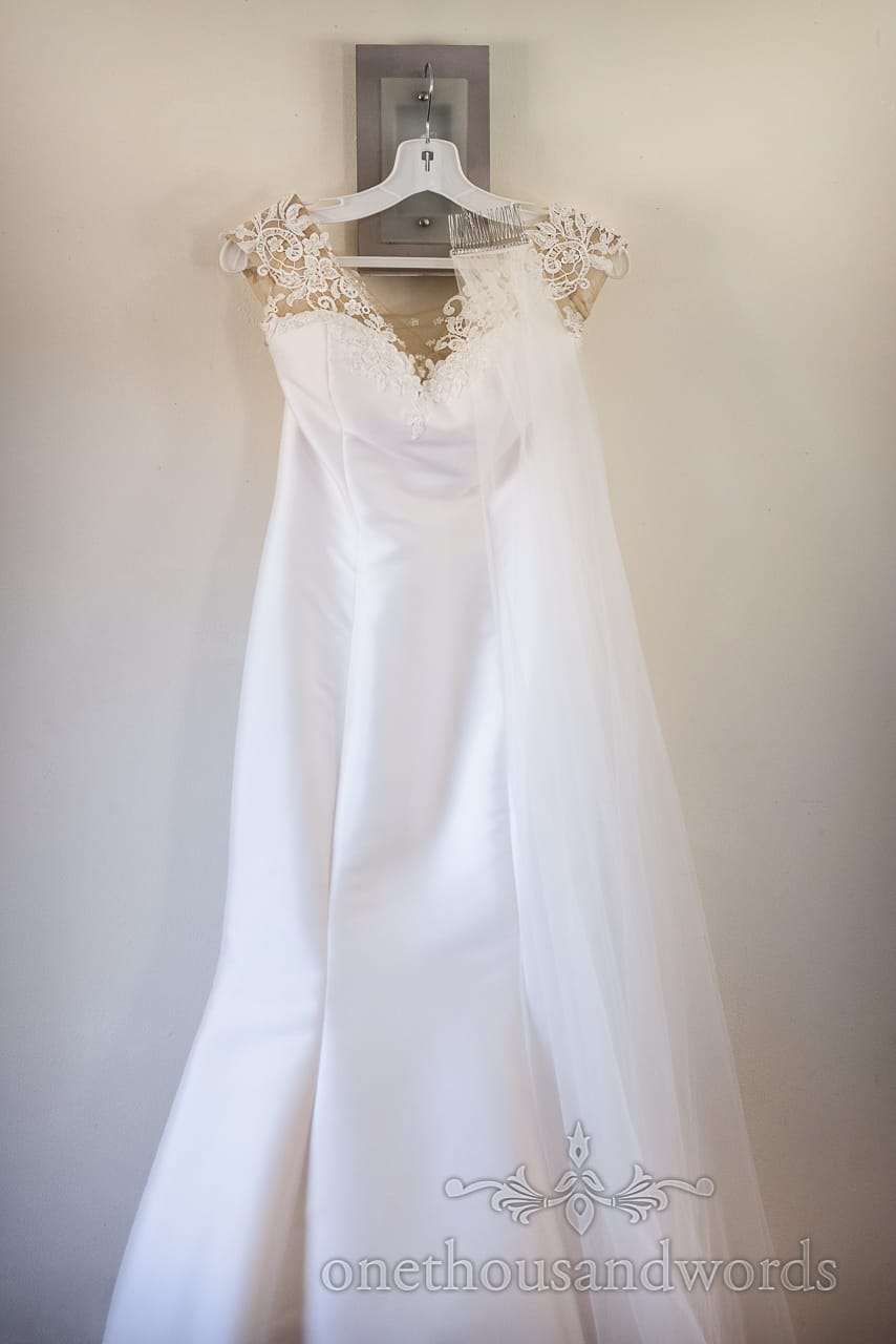 White mermaid wedding dress with lace detail on the shoulders hanging on modern light fitting with veil