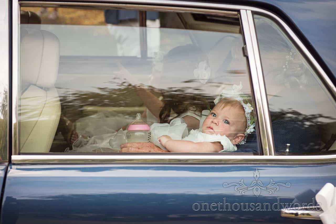 Documentary photograph of baby flower girl In white dress held on lap with milk bottle through wedding car window