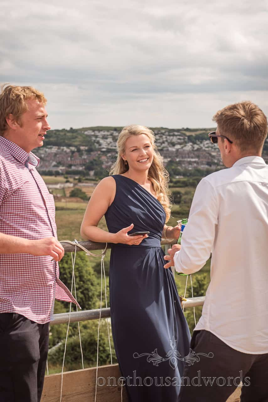 Beautiful blonde bridesmaid has conversation with wedding guests while leaning on balcony with Swanage in the background