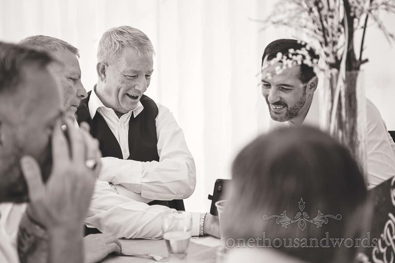 Black white wedding photographs of best man laughing at mobile phone during marquee reception