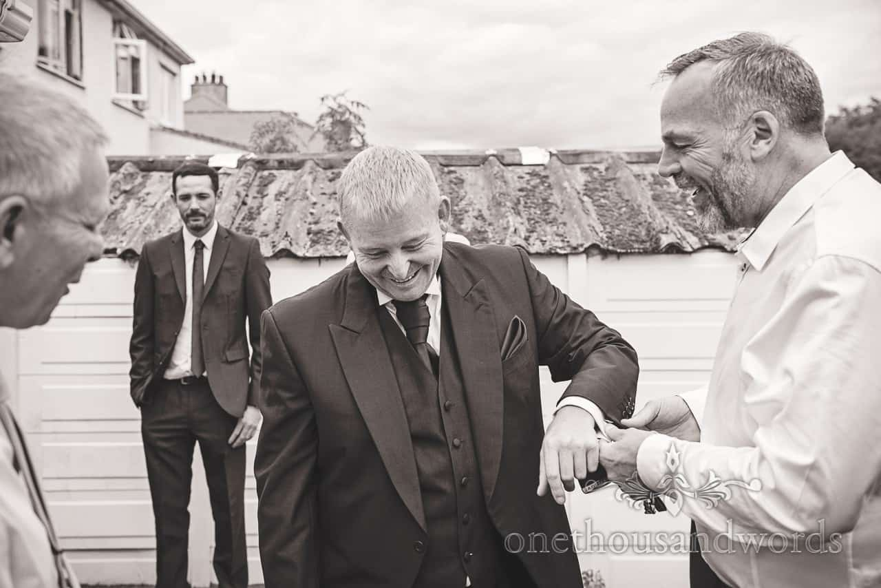 Black and white groom preparation photograph of friends adjusting his suit