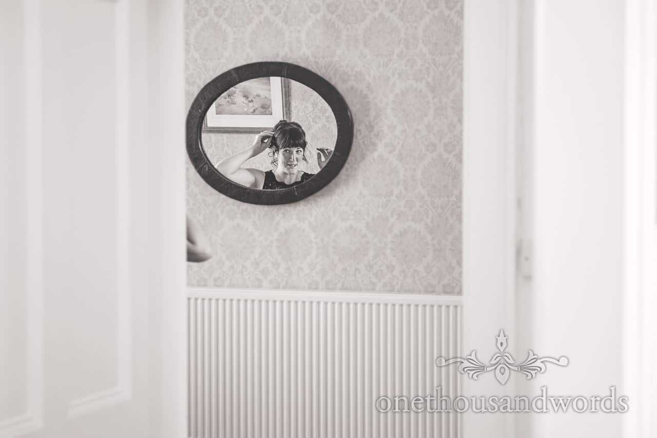 Black and white wedding photo of bridesmaid in oval mirror during morning preparations