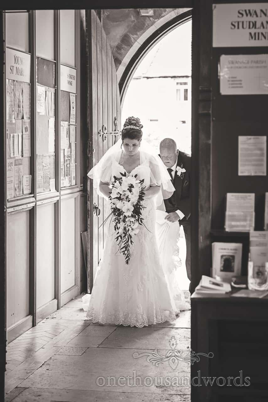 Black and white wedding photograph of bride having dress adjusted by father while waiting in church doorway