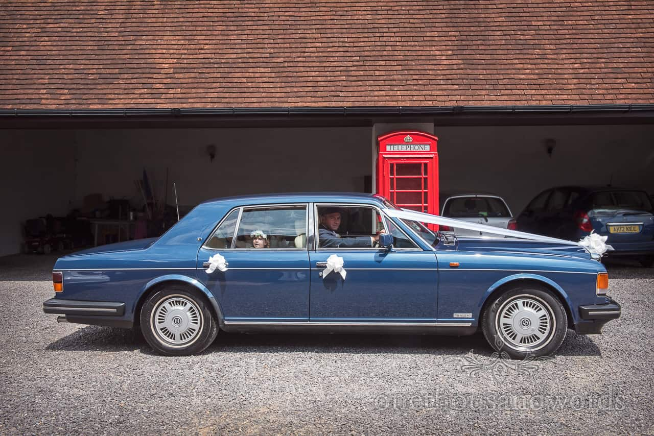 Blue Bentley wedding car with ribbons outside garage with British red phone box