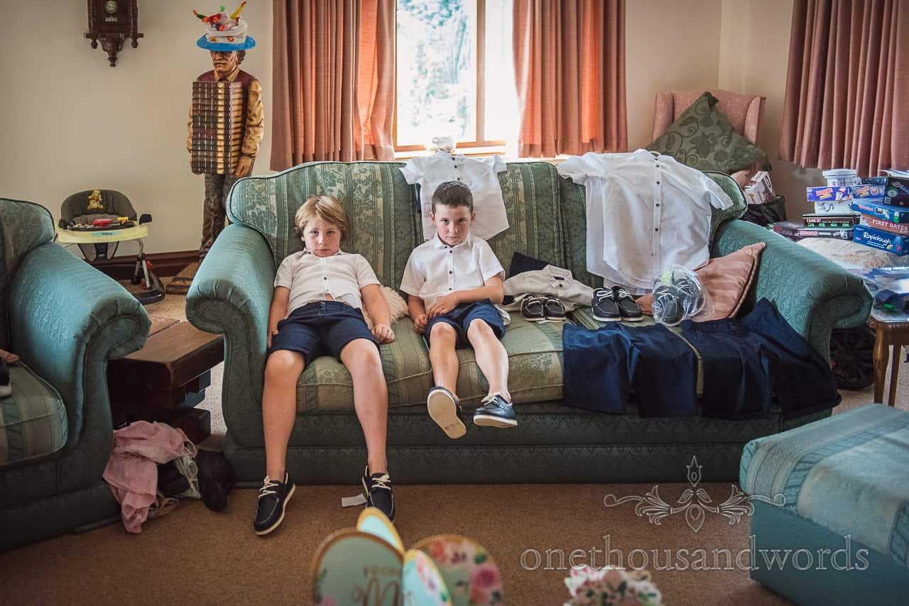 Bored looking page boys in blue shorts and white shirts sit on sofa during wedding morning preparations at brides family home