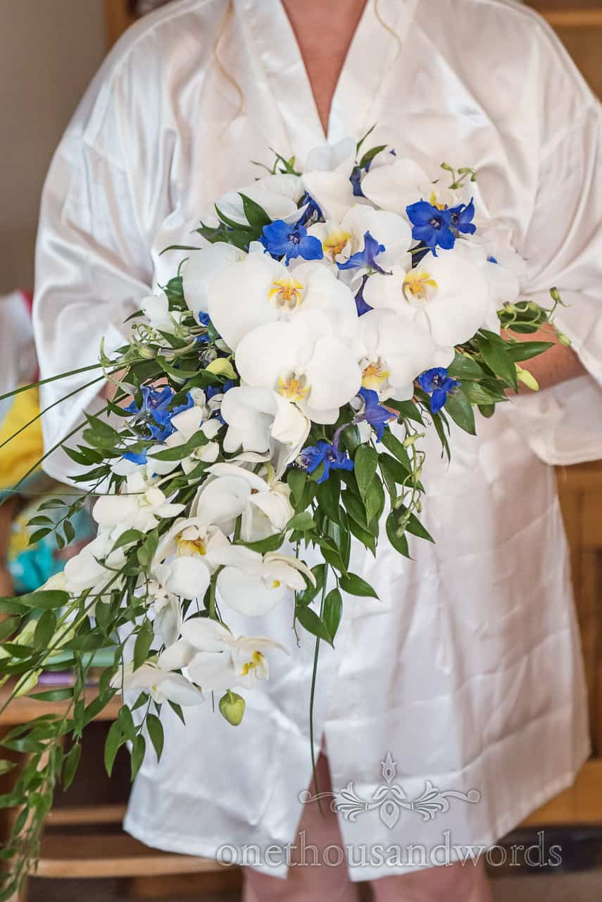 Photograph of bridal bouquet flower spray of white orchids and blue flowers with green foliage held by bride on wedding morning