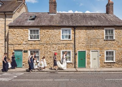 Bridal party walks along the streets on way to Sherborne Abbey wedding