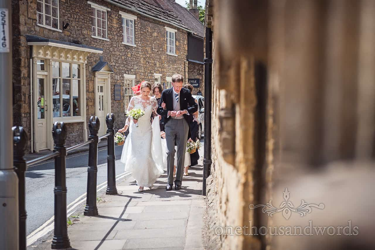 Bride and bridal party walk along the streets before Sherborne abbey wedding in Dorset