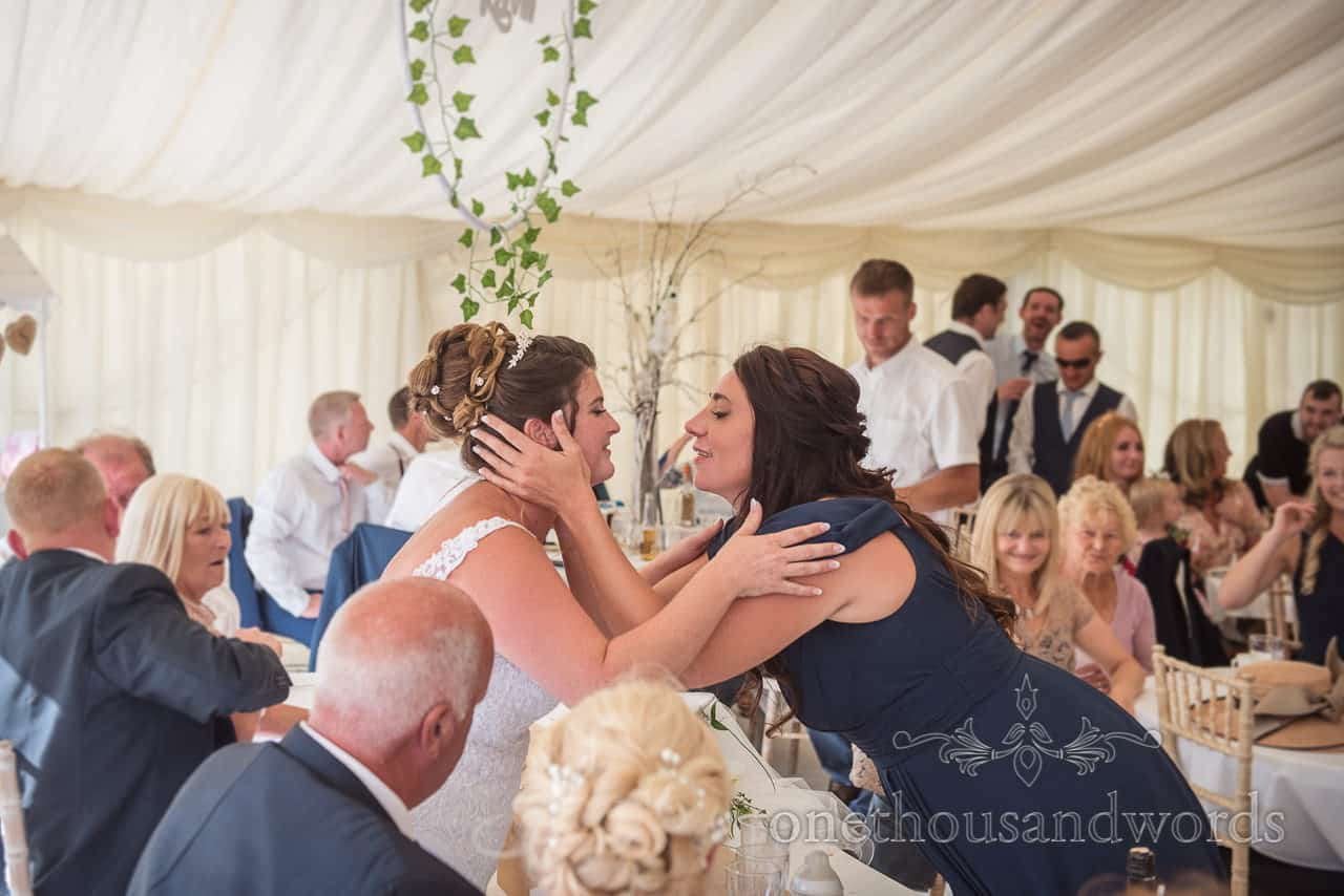 Documentary photograph of bride and bridesmaid embrace after brides wedding speech at marquee reception