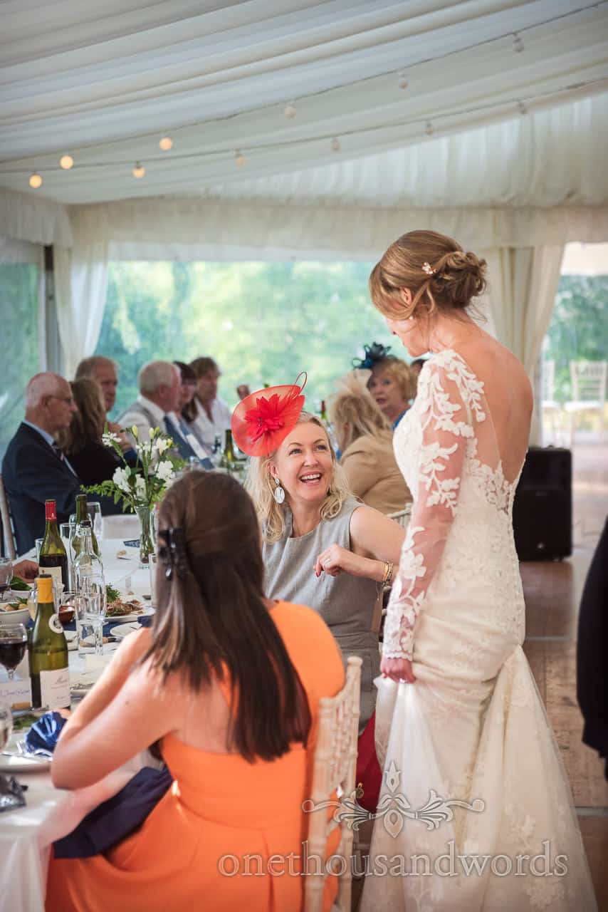 Bride chats with wedding guest at Sherborne castle marquee reception