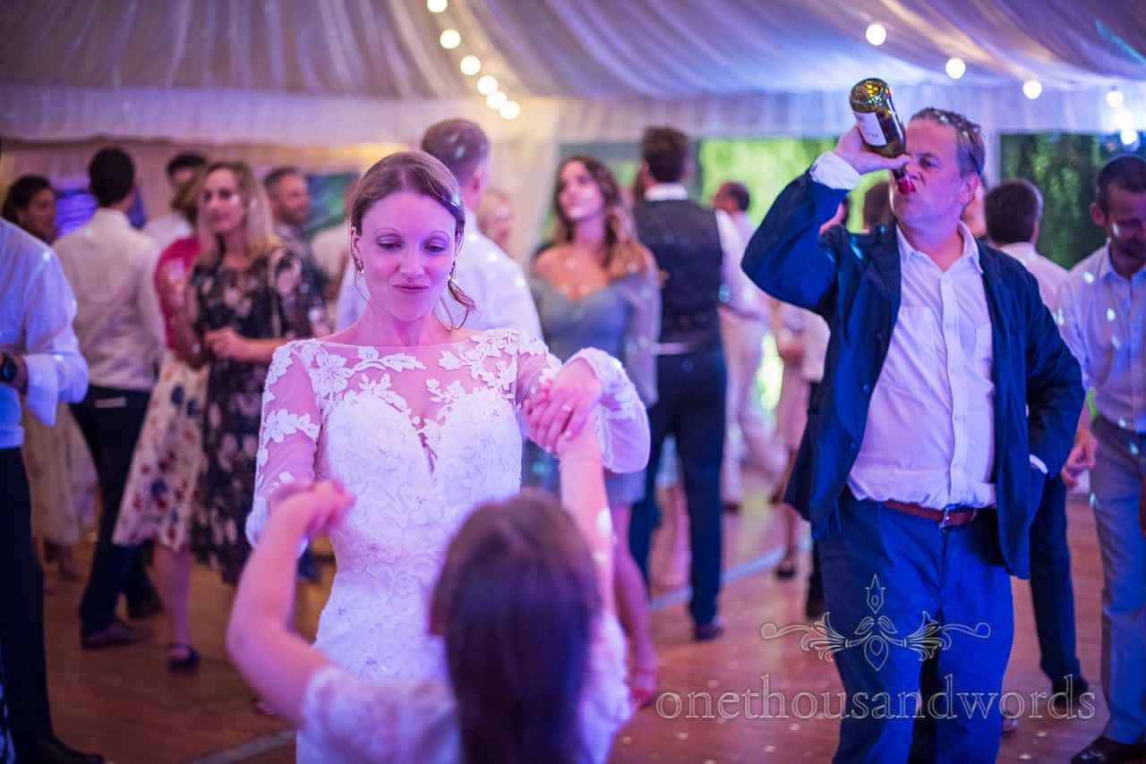 Bride dances with flower girl while wedding guest drinking bottle wine during marquee reception