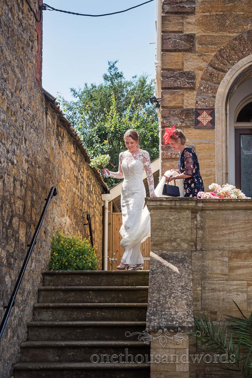 Bride and mother descend stone staircase before Sherborne Abbey wedding in Dorset