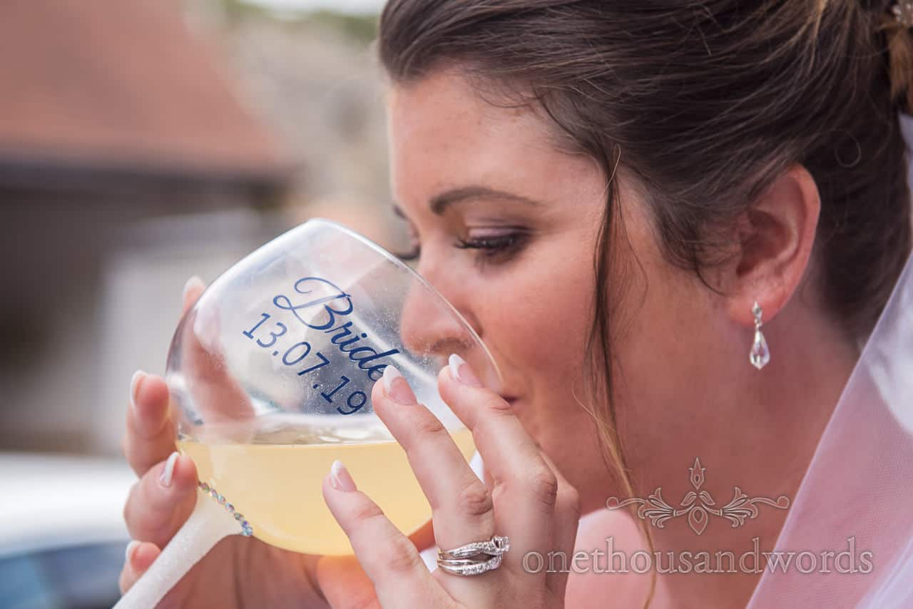 Documentary photograph of bride drinking from huge personalised wine cocktail glass