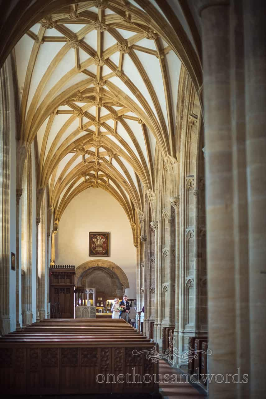 Bride and father wait under archways of Sherborne Abbey before ceremony