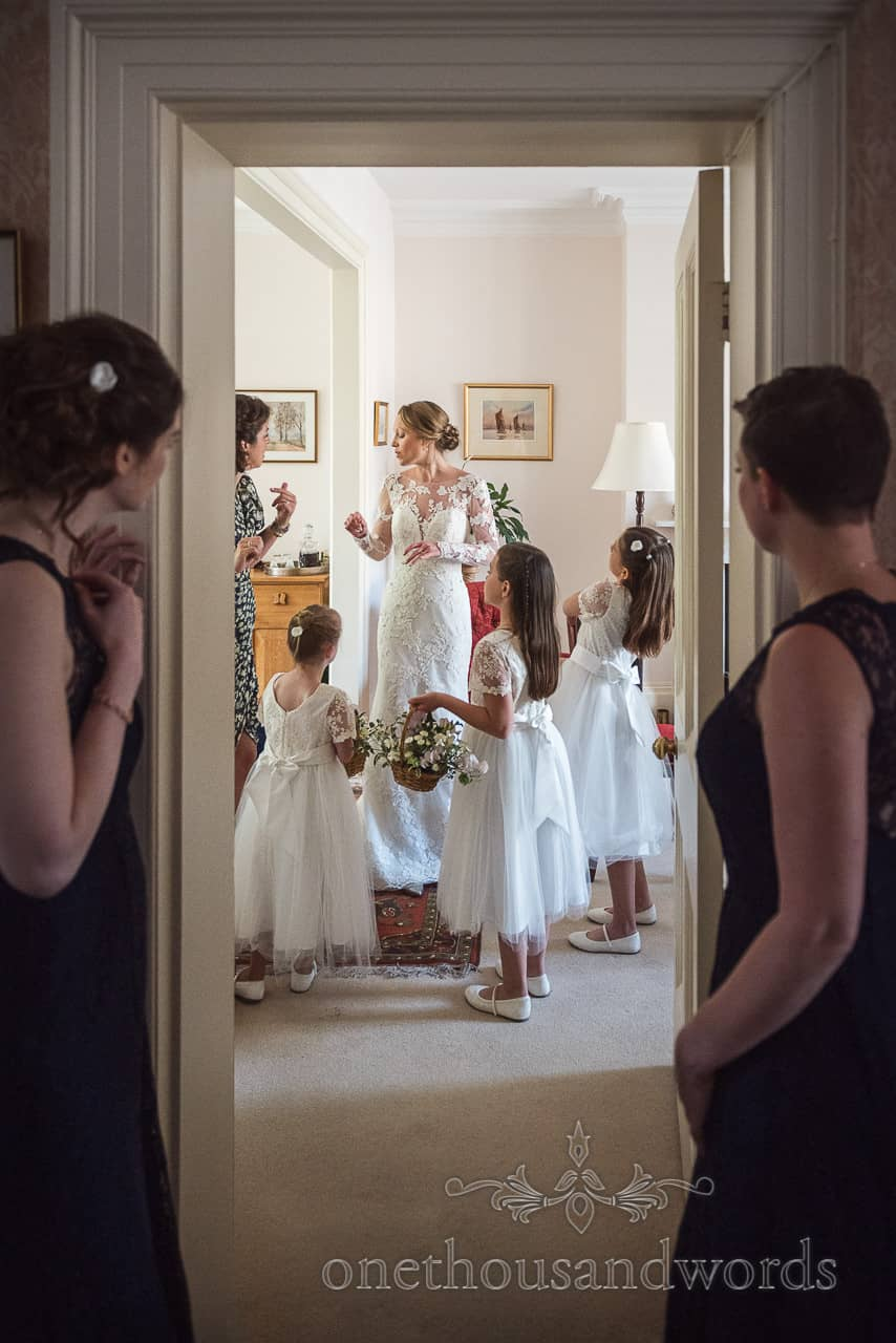 Bride and flower girls watched by bridesmaids through doorway on wedding morning
