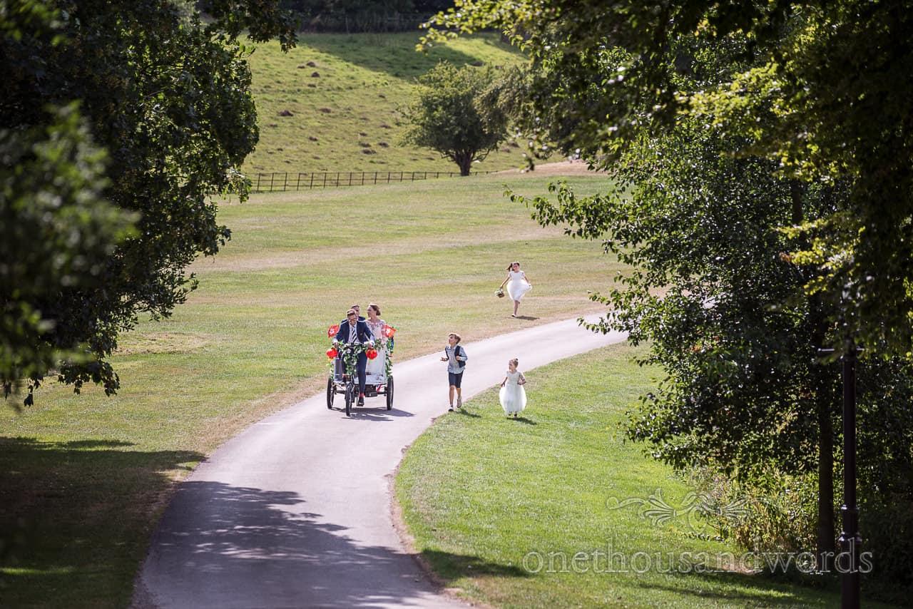 Bride and groom arrive at Sherborne castle wedding by rickshaw trike