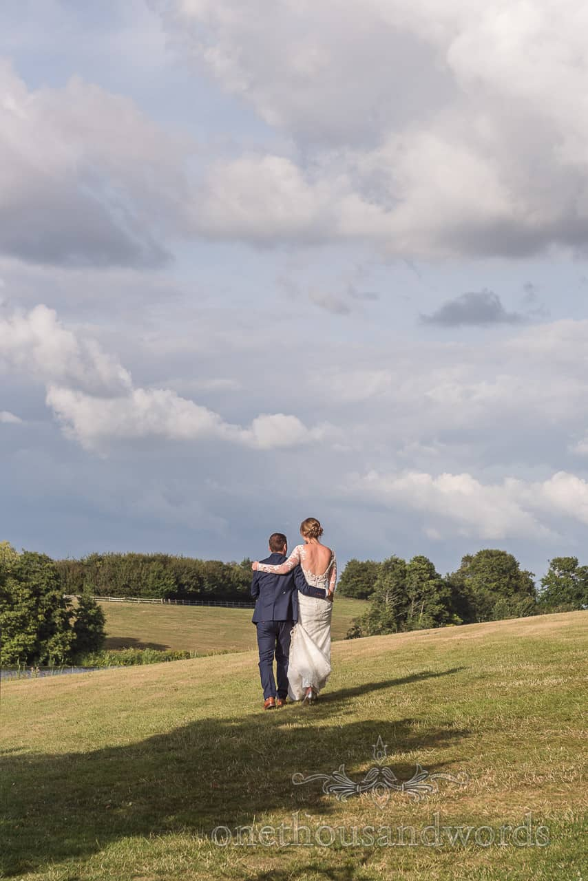 Bride and groom take countryside walk during Sherborne Castle wedding reception
