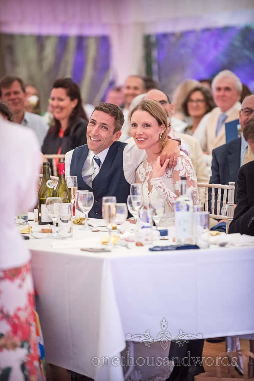 Bride and groom cuddle up while watching wedding speeches in marquee