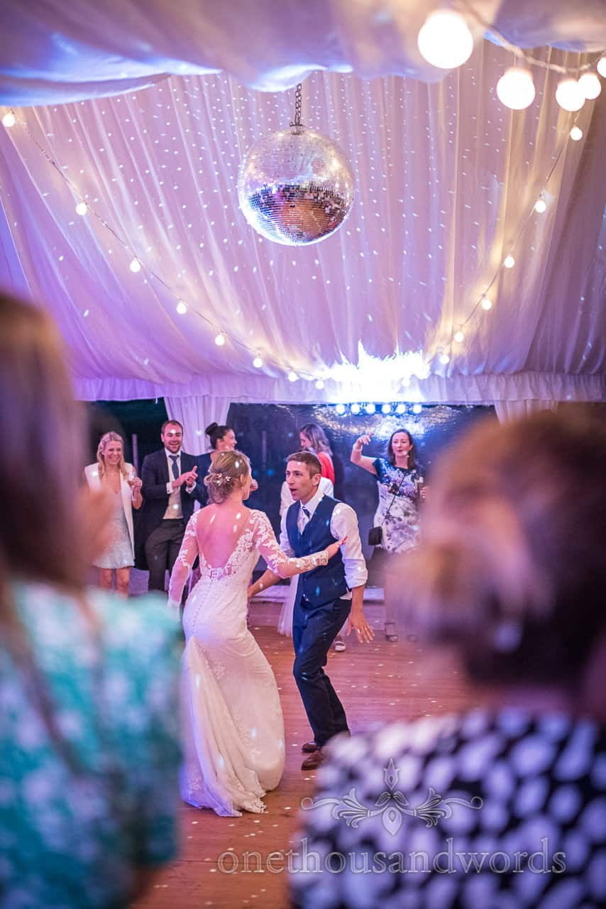 Bride and groom dance under disco ball at Sherborne Castle wedding photographs
