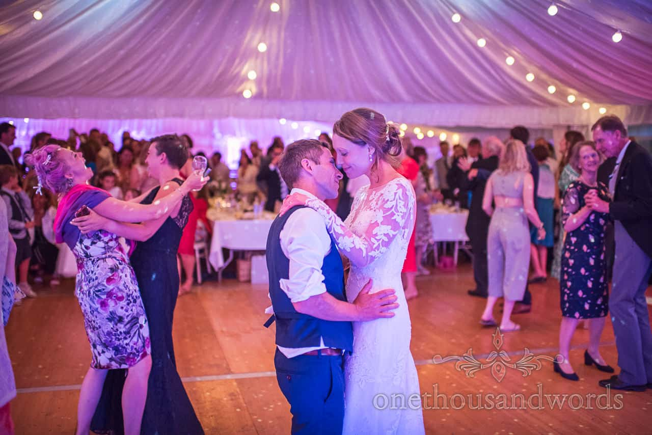 Bride and groom dance with wedding guests at Sherborne Castle wedding marquee reception