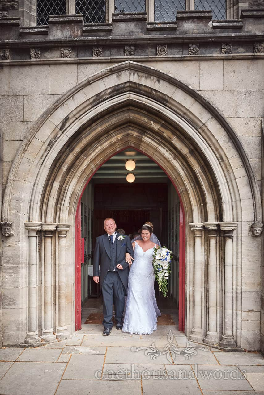 Documentary photograph of bride and groom exit church arched stone doorway in Swanage
