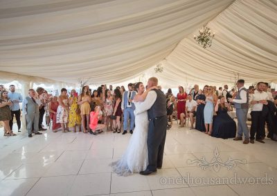 Bride And groom take first dance on shiny white dance floor marquee watched by wedding guests