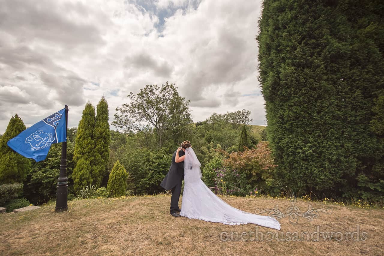 Bride and groom hug in gardens as Everton FC flag flies