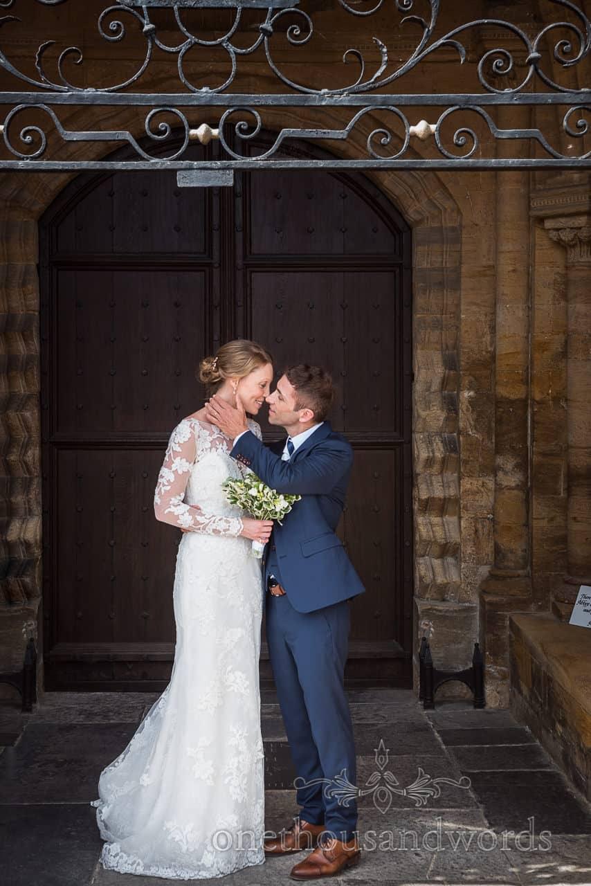 Bride and groom kiss in Sherborne Abbey wedding venue doorway
