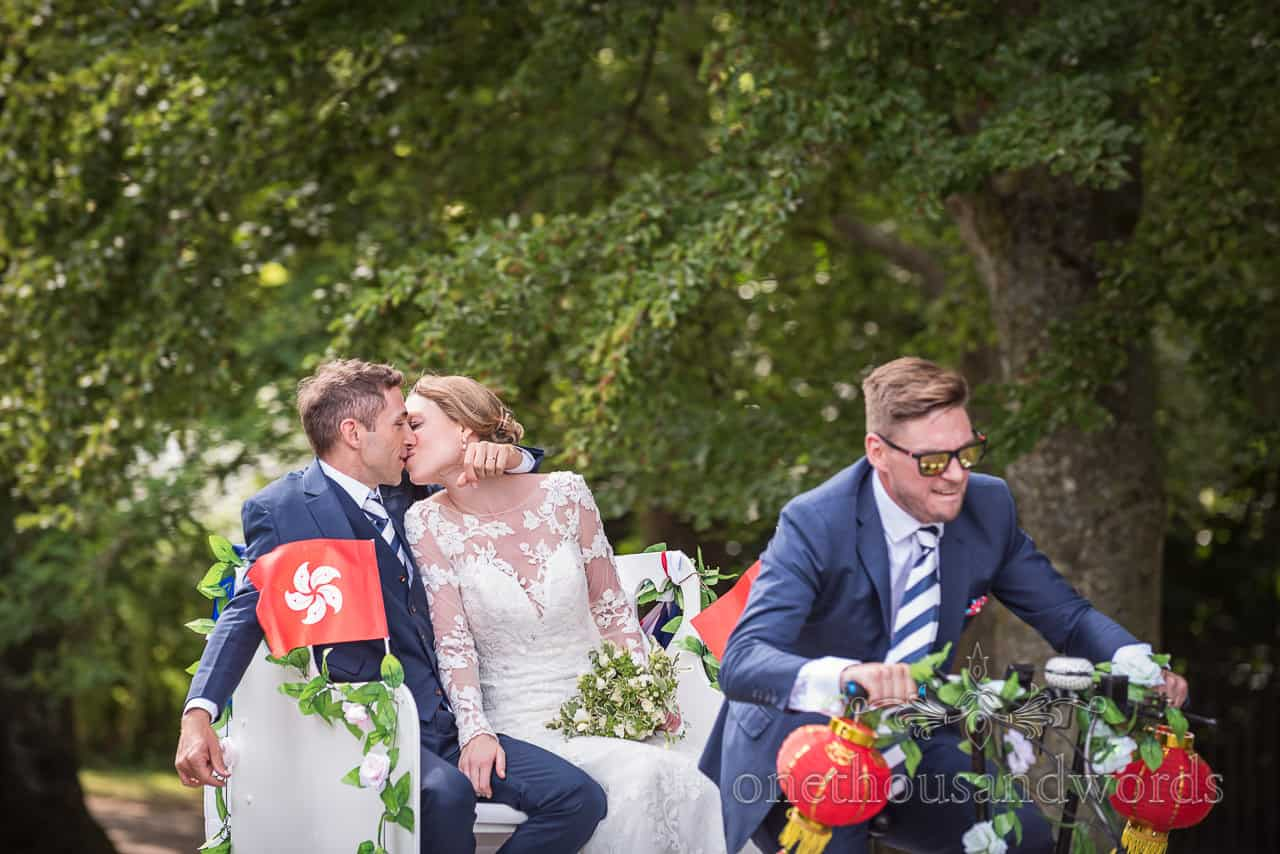 Bride and groom kissing in back of wedding rickshaw trike on way to castle