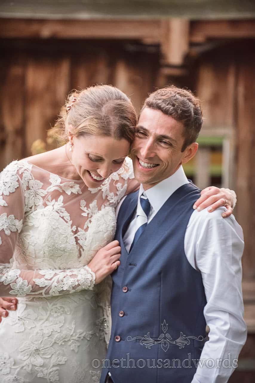 Bride and groom laughing couple shot at Sherborne Castle boat house wedding photograph by one thousand words