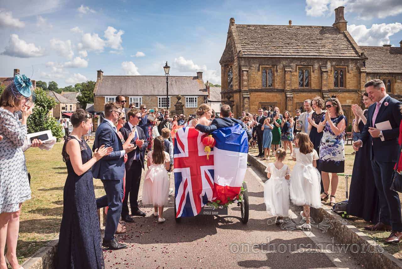 Bride and groom leave Sherborne Abbey wedding venue in rickshaw trike with united Kingdom and French flags