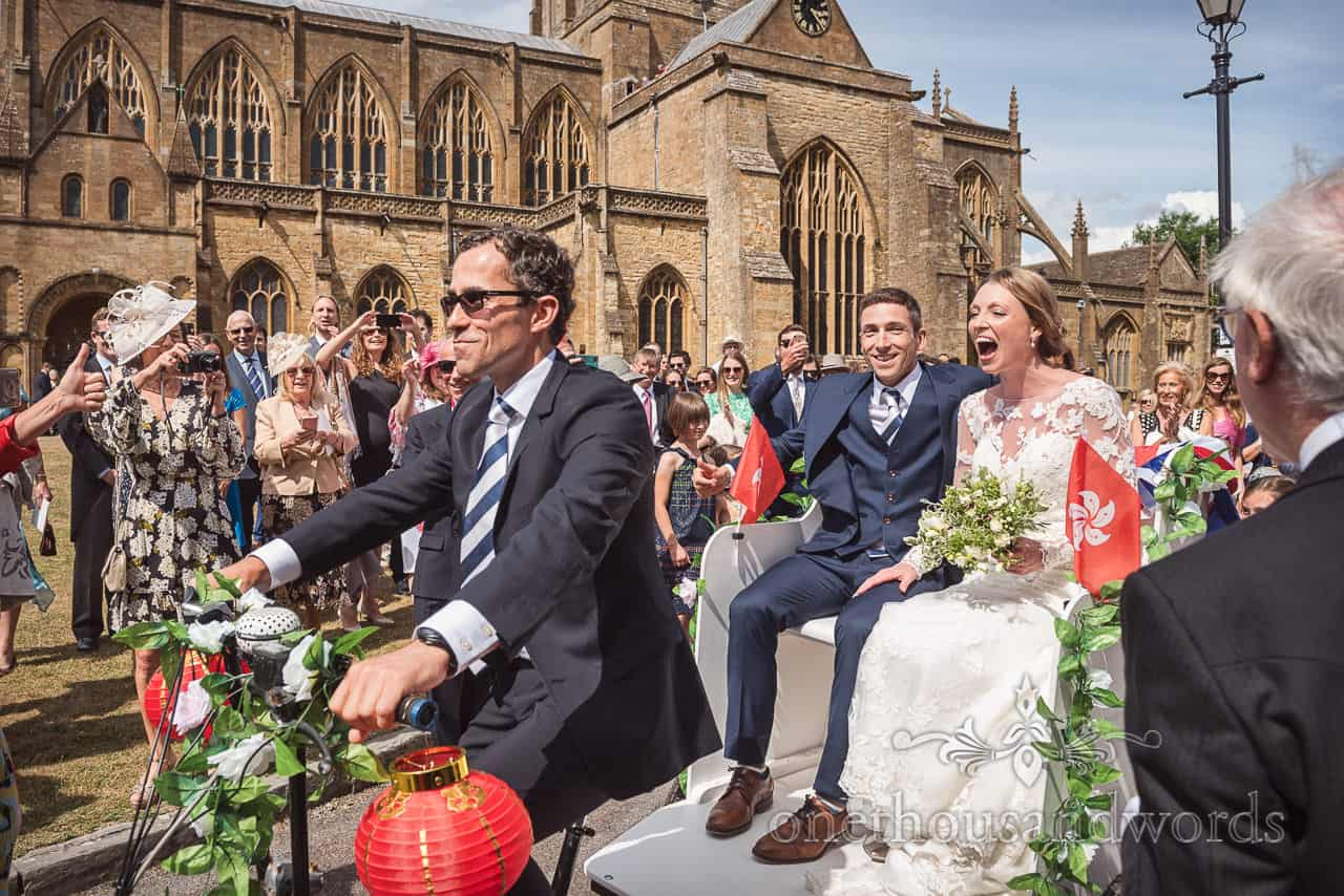 Documentary wedding photograph of excited bride and groom leaving Sherborne Abbey wedding venue in rickshaw trike