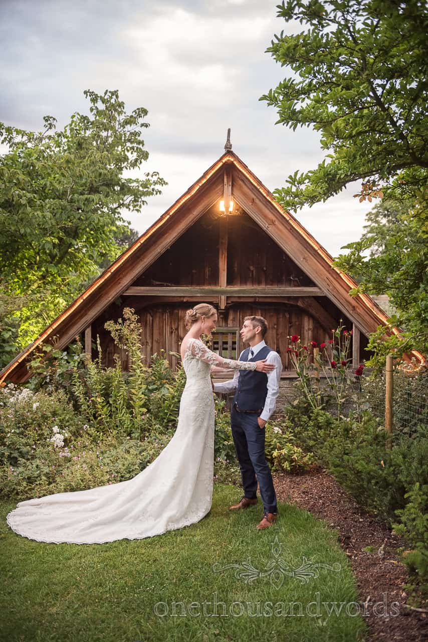 Bride and groom embrace at Sherborne Castle wedding venue boat house photograph by one thousand words wedding photography