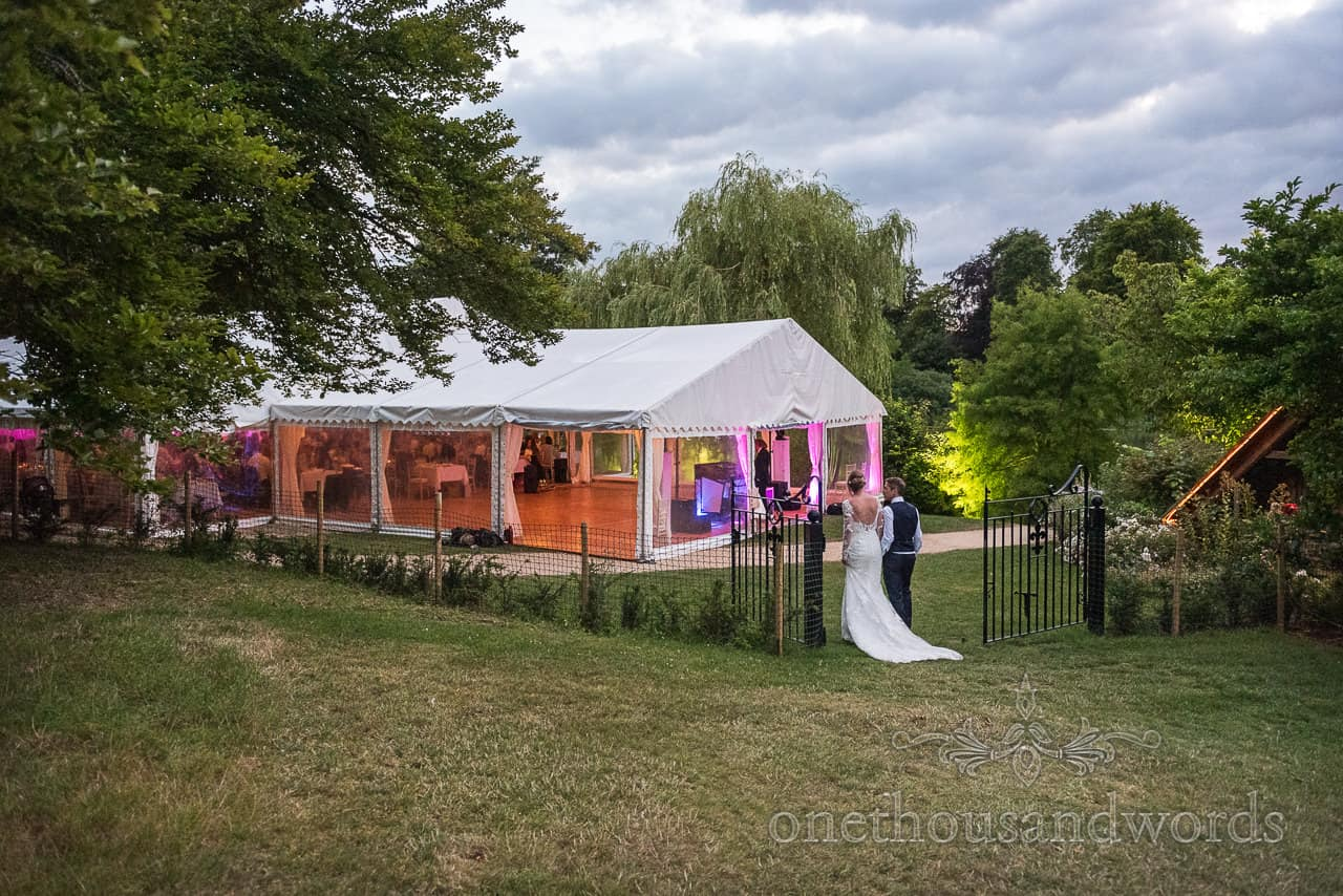 Bride and groom at Sherborne Castle wedding marquee glowing at night wedding photograph by one thousand words photographers