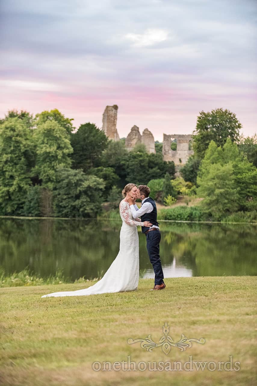 Bride and groom kiss at sunset at Sherborne Castle wedding photographs next to lake with old castle ruins in background