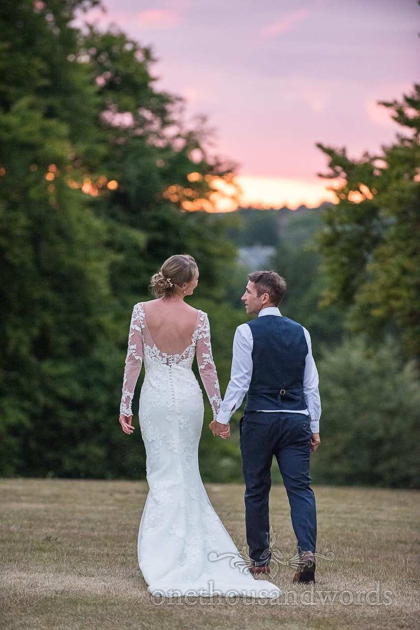 Bride and groom walk hand in hand in countryside gardens at sunset from Sherborne Castle wedding photographs