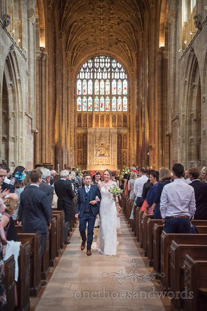 Happy bride and groom walk arm in arm down the aisle as husband and wife after Sherborne Abbey wedding ceremony