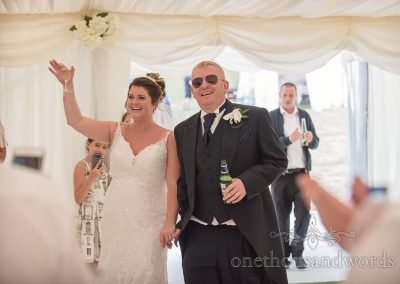 Bride and groom walk into wedding marquee to rapturous applause at Swanage reception