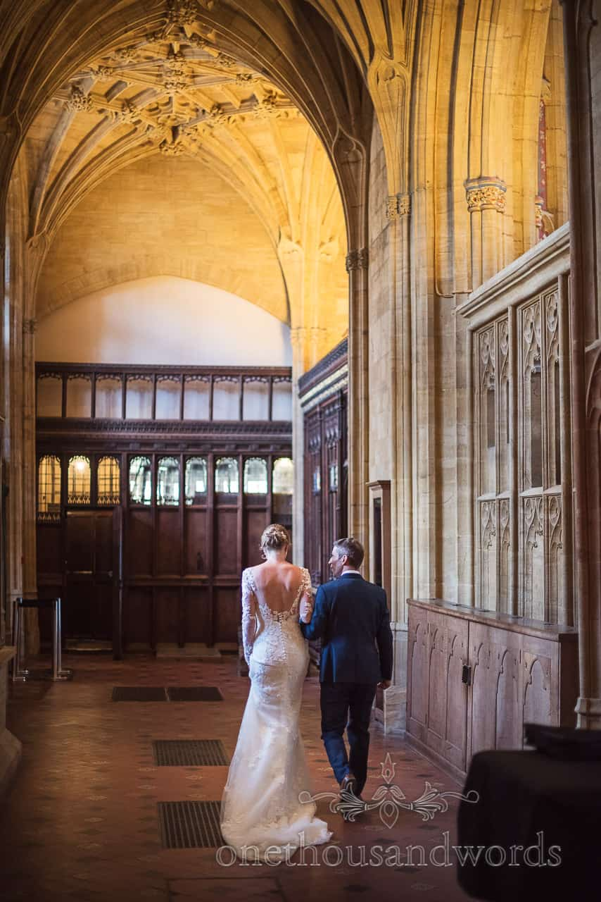 Bride and groom walk through stunning carved stone archways architecture of Sherborne Abbey wedding venue