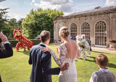 Bride and groom watch traditional Chinese Dragon dance at Sherborne Castle wedding reception in front of the Orangery