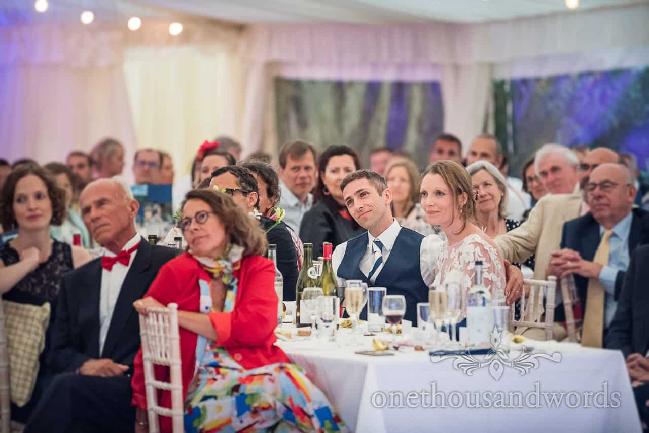 Bride and groom watch wedding speeches in amongst their wedding guests in marquee evening reception