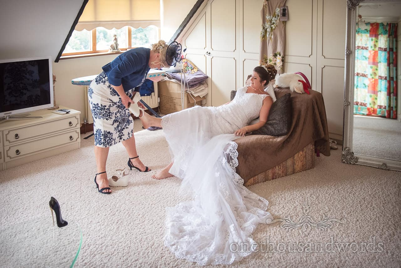 Bride is helped with wedding shoes by mother during wedding morning preparation