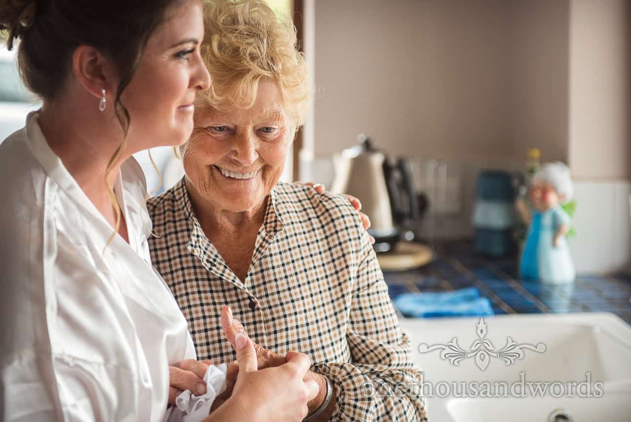 Documentary wedding photograph of bride hugging grandmother on wedding morning