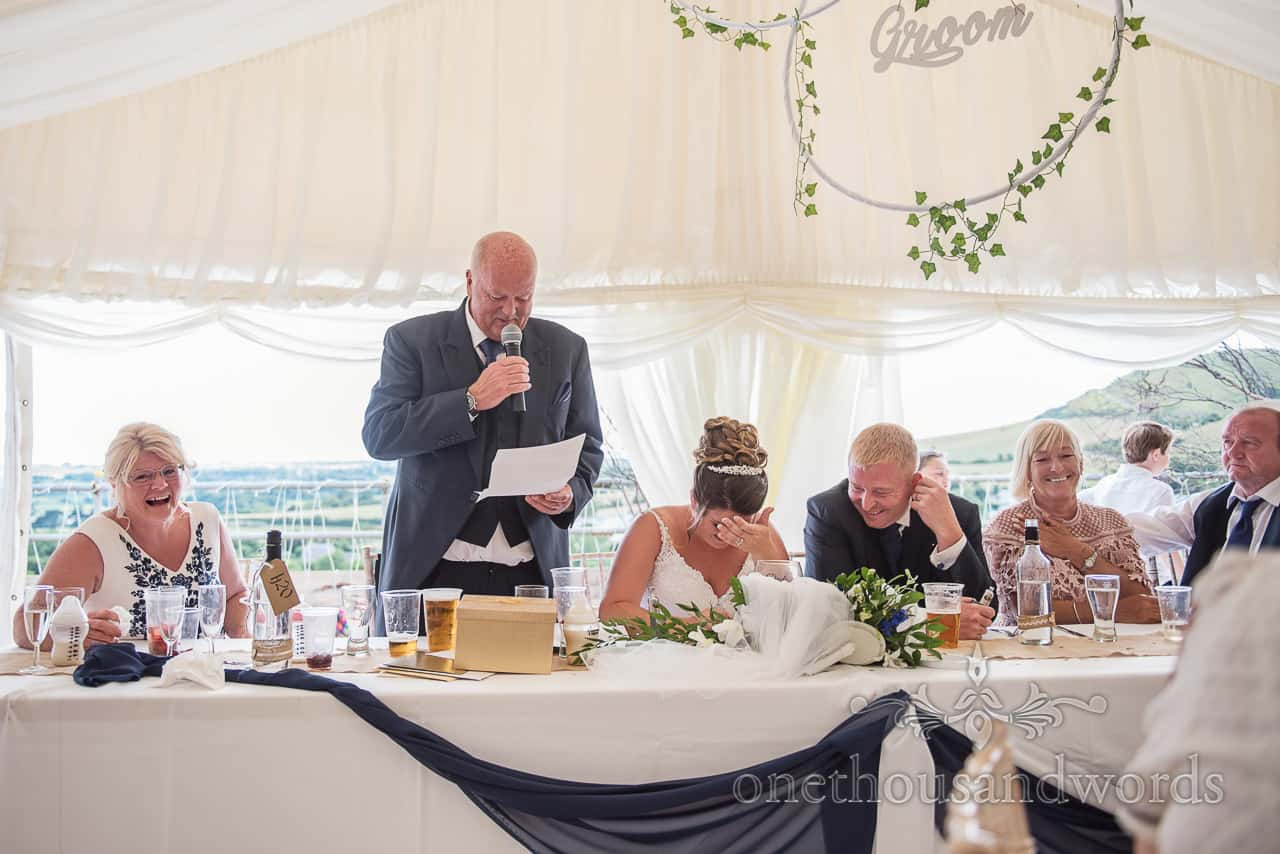 Bride holds her head with her hand during the father of the bride speech at top table in wedding marquee
