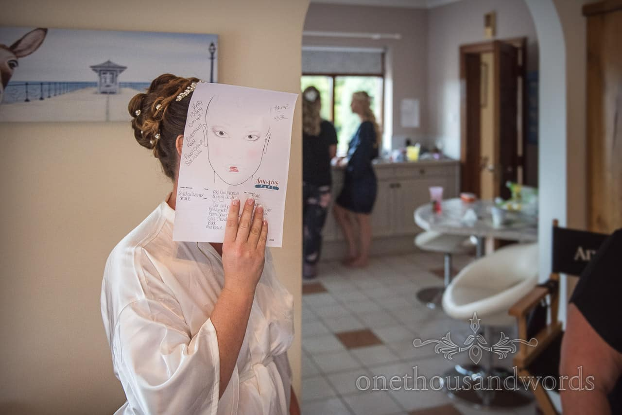 Bride holds wedding makeup plan picture in front of her face at bridal morning preparations