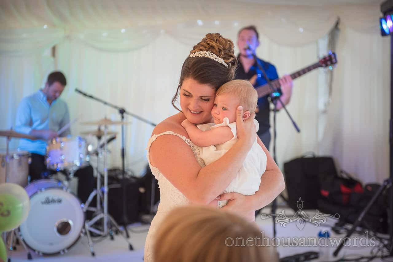 Bride hugs baby daughter as wedding band play in marquee at evening reception photograph by one thousand words photography