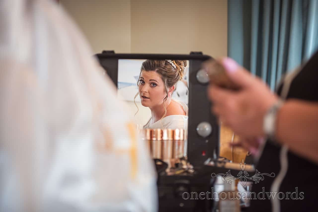 Bride looks at herself in makeup mirror during wedding morning preparation photographs