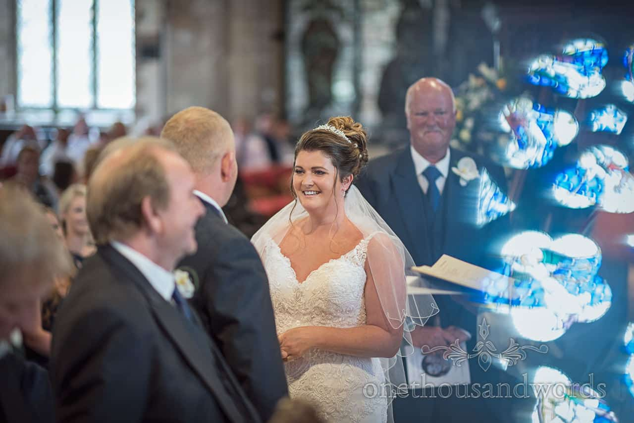 Bride smiles at groom during wedding vows in church with reflection of stained glass window