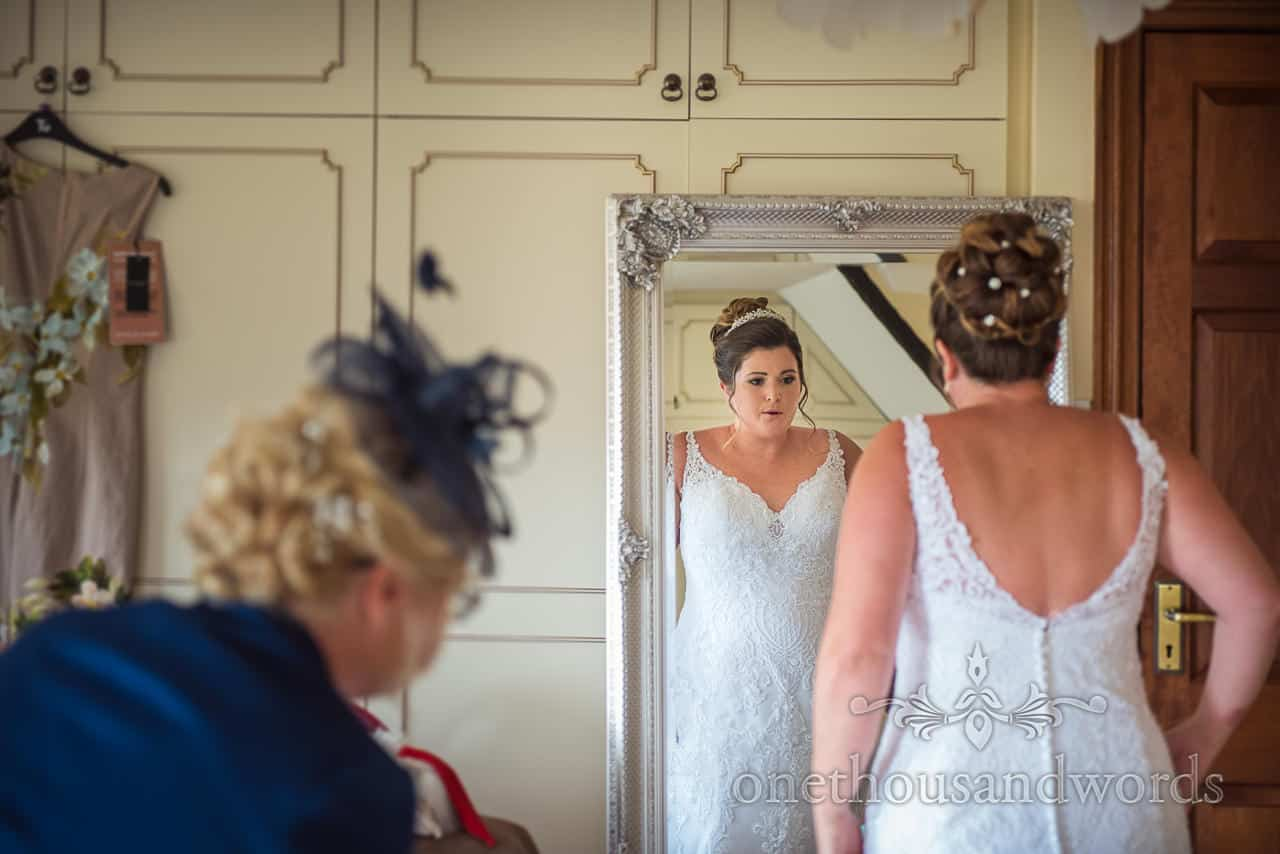 Bride takes deep breath as she looks in silver framed mirror as she is helped to put wedding dress on