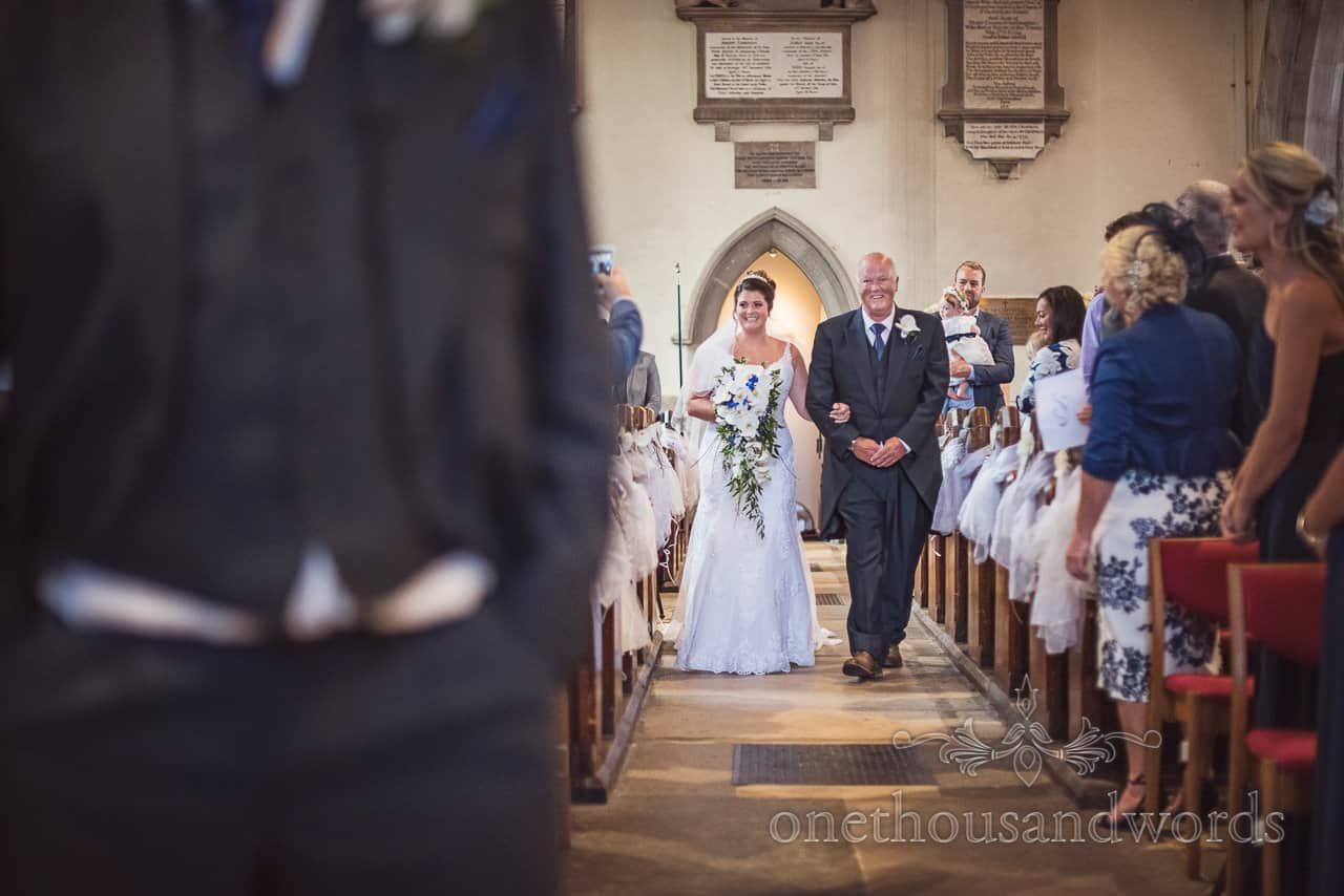 Bride is walked down the aisle by her father at Swanage church wedding ceremony in Dorset documentary wedding photograph